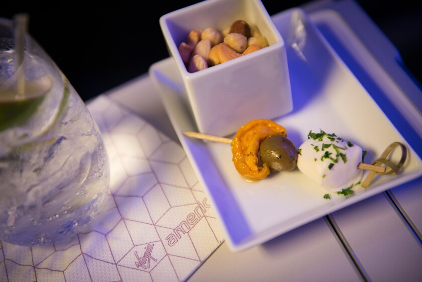 Virgin America added cocktail hors d'oeuvres to its onboard menu. Other airlines are improving their food selections as well.