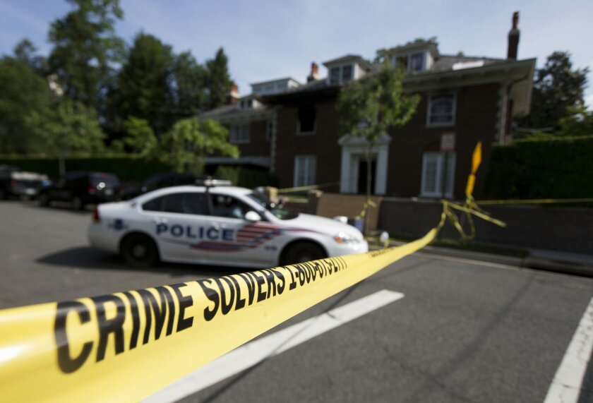 Washington police secure the vicinity around the fire-damaged multimillion-dollar home in northwest Washington, Wednesday, May 20, 2015, where four people were found dead May 14. Washington Police Chief Cathy Lanier earlier identified two of the victims found dead as 46-year-old Savvas Savopoulos a