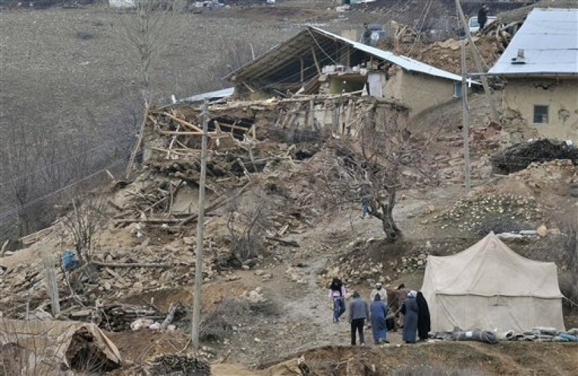 People walk in the debris of houses destroyed in an earthquake, in Okcular village in the eastern province of Elazig, Turkey, Monday, March 8, 2010. A strong, pre-dawn earthquake knocked down stone and mud-brick houses, barns and minarets in eastern Turkey on Monday, killing scores of people in fiv