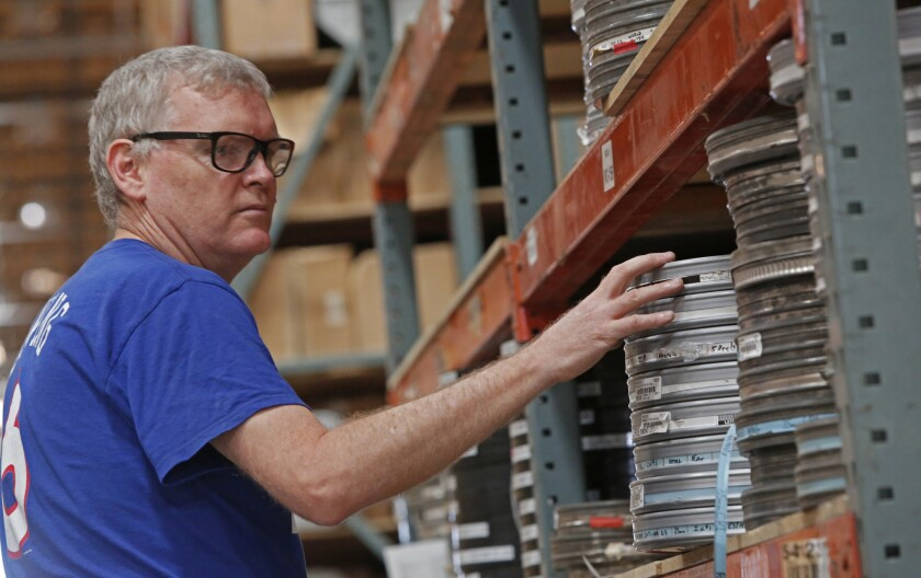Ed Carter from the Academy of Motion Picture Arts and Sciences sorts through old film prints from Deluxe Film in a warehouse in Lebec. Once sorted they will be sent to the Academy in Hollywood. (Anne Cusack/Los Angeles Times)