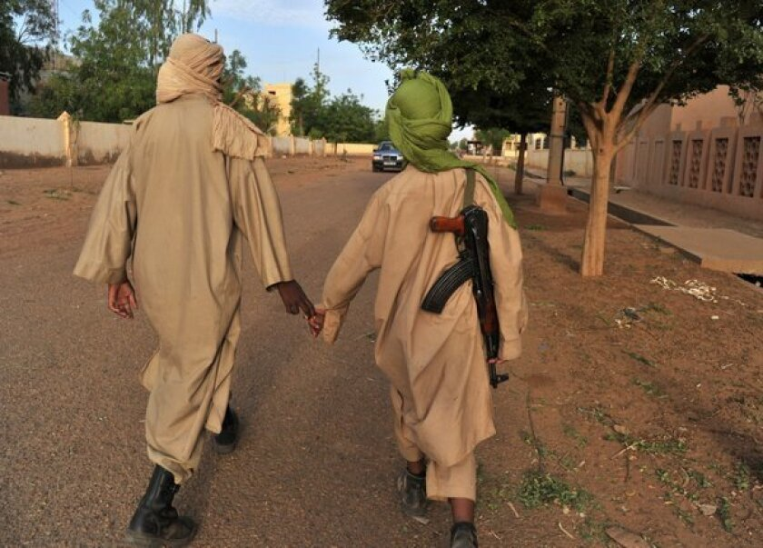 Fighters with the Islamist group Movement for Unity and Jihad in West Africa (MUJAO) walk through Gao, Mali.