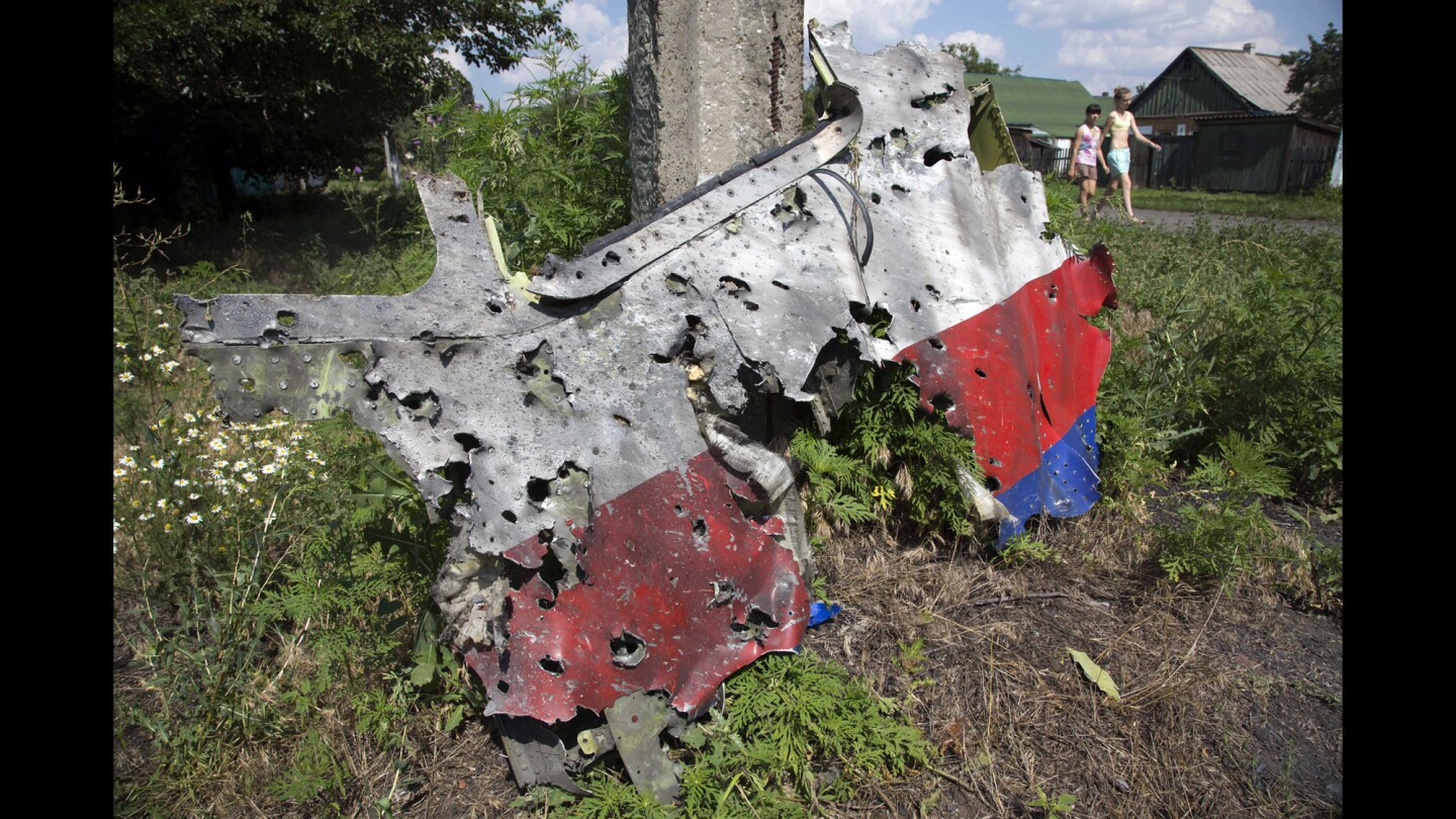 Children walk past a piece of the wreckage in the village of Petropavlivka in eastern Ukraine.