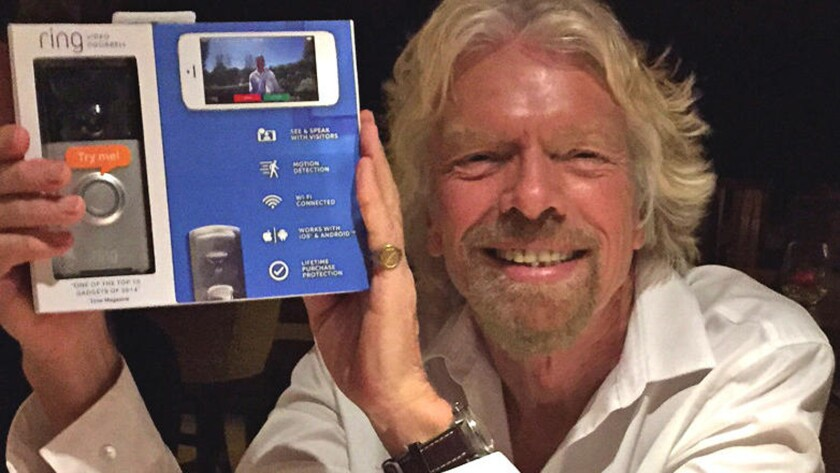 Richard Branson, founder of the Virgin Group, poses with a package for Ring, a $199 doorbell that has an Internet-connected video camera attached to it.