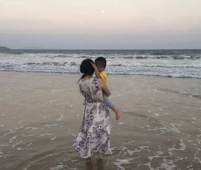 In this photo released by Zou Xiaoqi, Zou Xiaoqi, a single mother turned activist in Shanghai, holds her son as they visit a beach in Sanya, southern China's Hainan province in October, 2019. Zou, who has become a source of support for single moms ever since she started publicly campaigning for her maternity benefits, said that the cultural stigma around being a single mother is still very intense. (Zou Xiaoqi via AP)