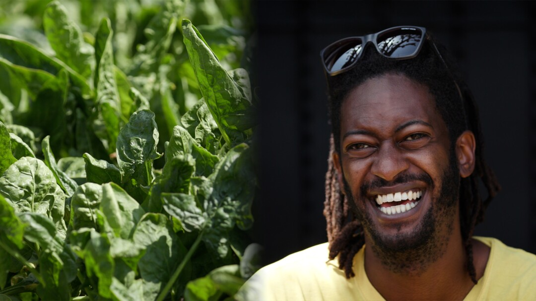 Urban gardener Jamiah Hargins, smiling, with dreads and sunglasses on his head.