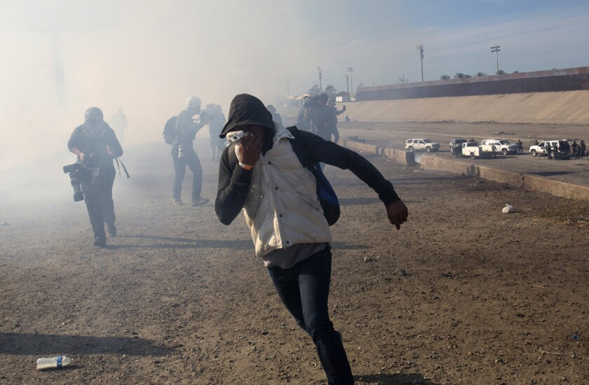 FILE - In this Nov. 25, 2018 file photo, a migrant runs from tear gas launched by U.S. agents, amid