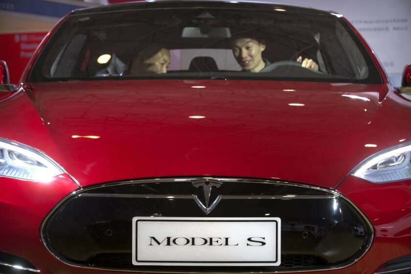 """FILE - In this Monday, April 25, 2016, file photo, a man sits behind the steering wheel of a Tesla Model S electric car on display at the Beijing International Automotive Exhibition in Beijing. Federal officials say the driver of a Tesla S sports car using the vehicle's """"autopilot"""" automated drivin"""
