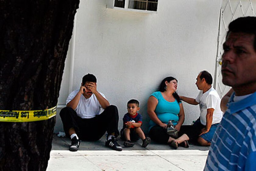 Family and friends of Ivan Valencia grieve, 30, after learning he had been shot to death at the corner of 55th Street and Broadway, near his home, on July 17. Five gangs operate in or near Valencia's South L.A. neighborhood, but he belonged to a gang whose turf is seven miles away.