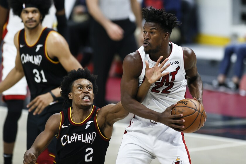 Miami Heat's Jimmy Butler (22) grabs a rebound against Cleveland Cavaliers' Collin Sexton (2) during the second half of an NBA basketball game, Saturday, May 1, 2021, in Cleveland. (AP Photo/Ron Schwane)