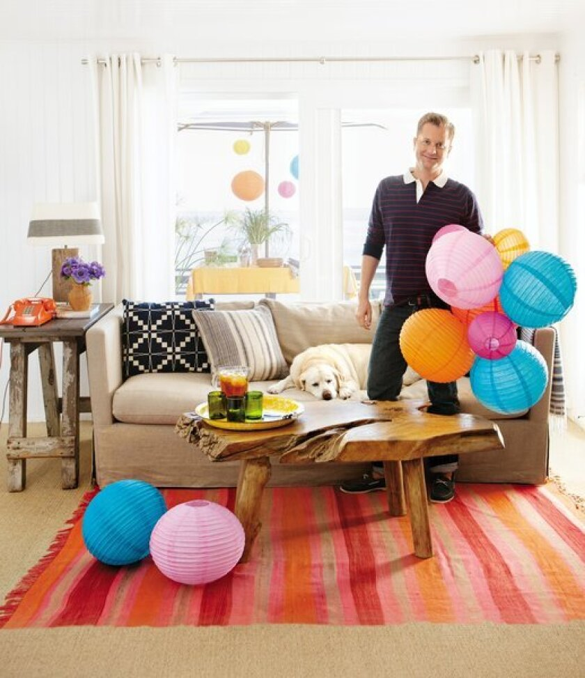 """In the photo that serves as the back cover of """"Nathan Turner's American Style,"""" the author prepares for a party at the Malibu beach apartment he shares with partner, interior designer Eric Hughes, while his faithful companion Daisy has a snooze. """"My approach to decorating and entertaining is all about finding new ways to live and celebrate with low effort and high style,"""" he writes. The unfussy apartment is painted in Benjamin Moore's high-gloss Super White for a """"modern nautical"""" feel. The floor is covered with inexpensive sisal and a colorful area rug; the grommet-topped curtains and hardware are from Ikea."""