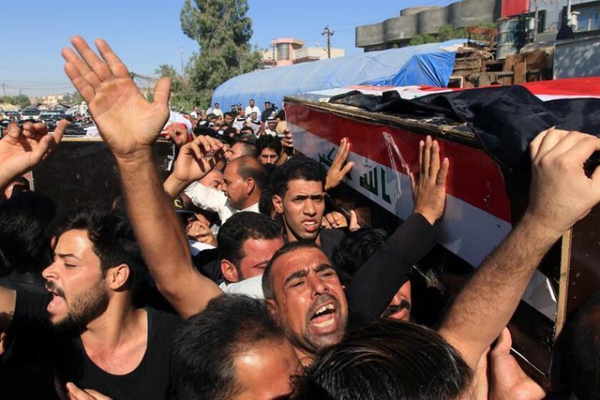 Varios iraquíes cargan con los restos mortales de un hombre que fue secuestrado y asesinado por yihadistas del grupo Estado Islámico (EI) , durante su funeral en Karbala (Irak) hoy, 28 de junio del 2018. EFE