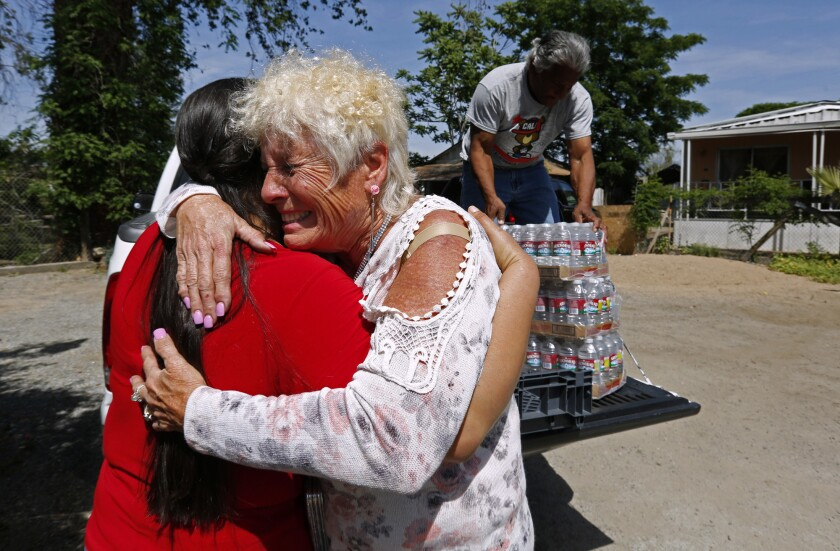 Donna Johnson, right, hugs Guillermina Andrade while delivering water with Ruben Perez to Andrade's home.