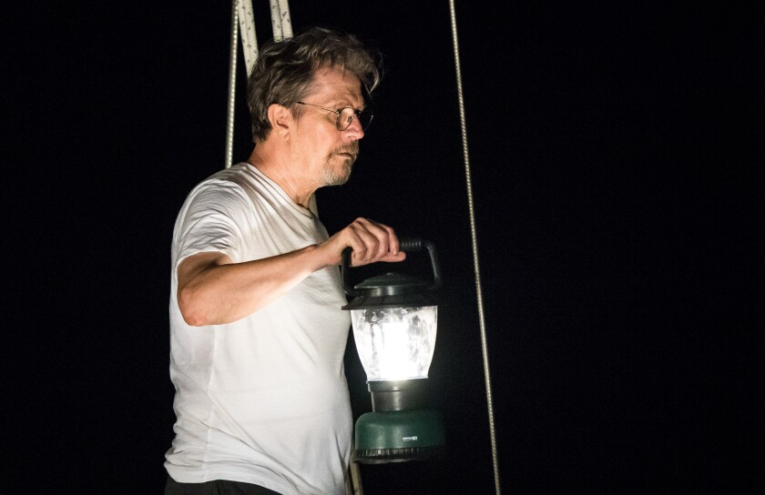 "Gary Oldman, holding a lantern, in ""Mary."""