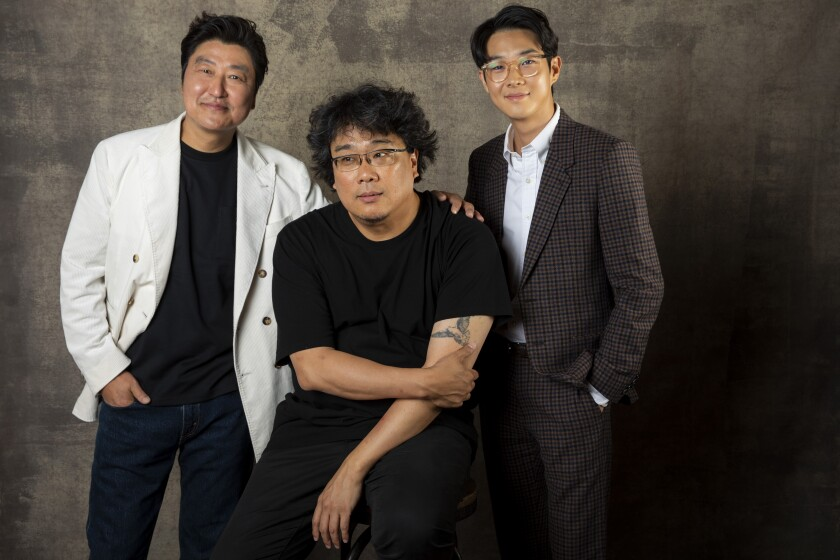 """Actor Song Kang Ho, left, director Bong Joon Ho and actor Choi Woo Shik, from the film """"Parasite,"""" in the L.A. Times photo studio at the Toronto International Film Festival on Sept. 7."""