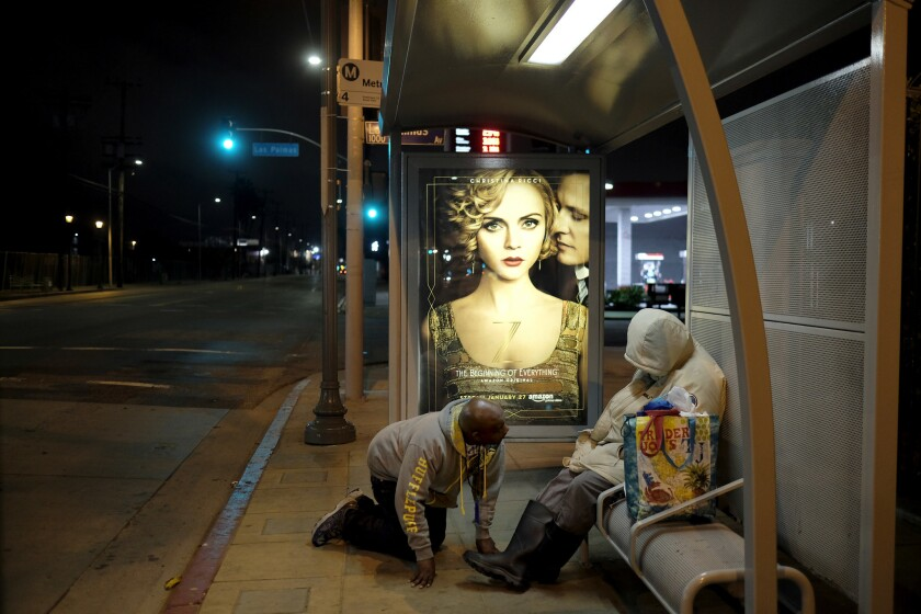 Outreach worker Anthony Ruffin kneels to check on a homeless woman sleeping on a bus bench