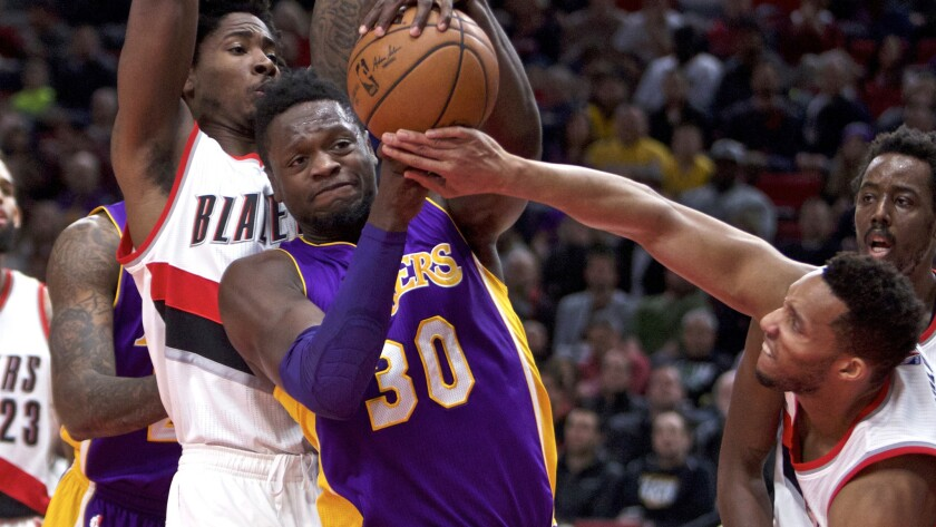 Lakers forward Julius Randle (30) tries to power his way to the basket against Trail Blazers center Ed Davis and guard Evan Turner, right, during the first half Thursday.