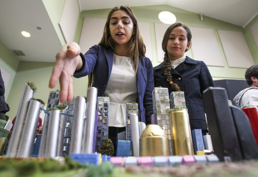 Eighth-graders from the Wildwood School, located in Los Angeles, Tess Levy, 13, left, and Emily Ribeiro, 14, explain their city named Vivace, that is fueled on 100 percent renewable energy, during the Future City Competition at The Rhoades School in Encinitas on Saturday.