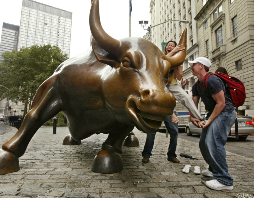 FILE - In this Aug. 16, 2004 file photo, a passerby, right, helps a woman from San Jose, Calif., mount a statue of a bull at the foot of Broadway in the financial district in New York. It's a new record for stocks, but it sure doesn't feel like it. The biggest gainers in the past year are fuddy-duddy utilities. Investors are cowering for cover in gold. And the best they're hoping for in the current earnings season is that profits don't fall as much as they initially feared. It's the second-longest bull market in history, and its old age is showing. (AP Photo/Kathy Willens, File)