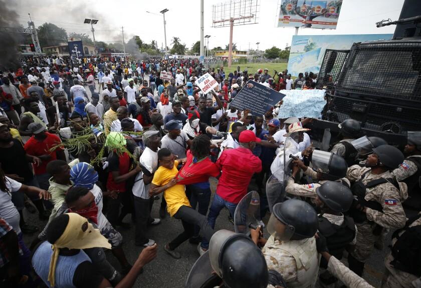 درگیری پلیس با تجهیزات ضد شورش با معترضین در لبه یک گروه بزرگ