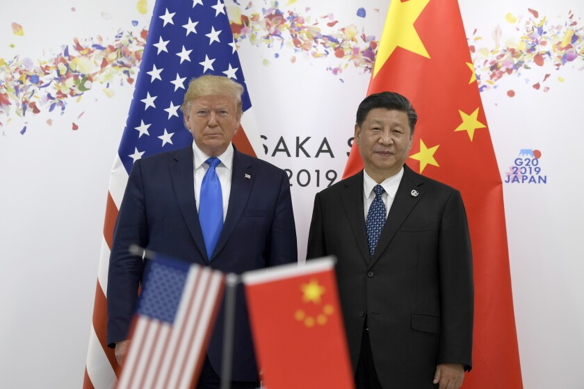 FILE - In this June 29, 2019, file photo President Donald Trump, left, poses for a photo with Chinese President Xi Jinping during a meeting on the sidelines of the G-20 summit in Osaka, Japan. China has fast become a top election issue as President Donald Trump and Democrat Joe Biden engage in a verbal brawl over who's better at playing the tough guy against Beijing. (AP Photo/Susan Walsh, File)