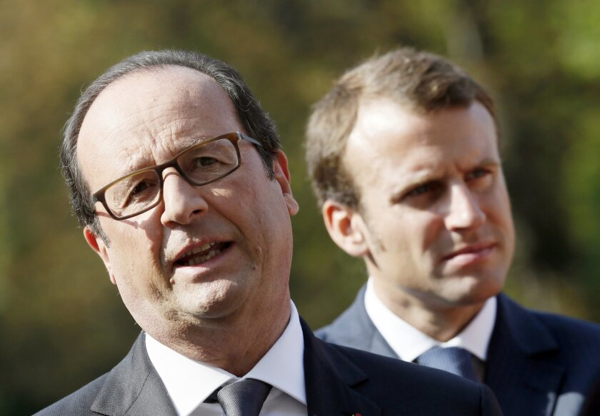 """French President François Hollande, left, poses Economy Minister Emmanuel Macron following the presentation of the """"34 plans for the new industrial France"""" Tuesday, Sept. 9, 2014 at the Elysee Palace in Paris. (AP Photo/Patrick Kovarik, Pool)"""