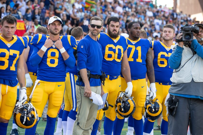 Rams offensive lineman Chandler Brewer (67, right) stands with teammates on the sideline.