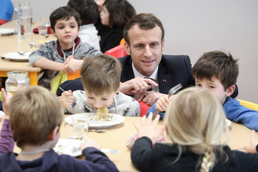 FILE - In this Jan.18, 2019 file photo, French President Emmanuel Macron meets pupils as he visits a school canteen in Saint-Sozy, southwestern France. By taking meat off the menu at school canteens, the Green Party mayor of Lyon has kicked up a storm of protest and debate in a country increasingly asking questions about the environmental costs of its meaty dietary habits. With a meatless four-course meal that Lyon City Hall says will be quicker and easier to serve to children who must be kept socially distanced while eating lunch to avoid coronavirus infections. (Ludovic Marin/Pool Photo via AP, FILE)