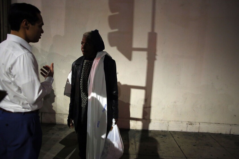 U.S. Housing and Urban Development Secretary Julian Castro meets with Jennifer Campbell, who is homeless, along skid row in Los Angeles in January.