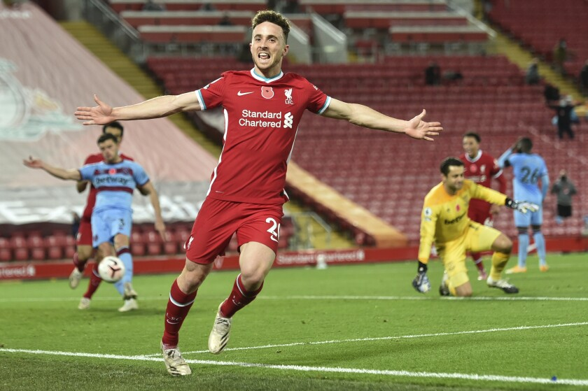 Liverpool's Diogo Jota celebrates after he scores his sides second goal during the English Premier League soccer match between Liverpool and West Ham United at Anfield stadium in Liverpool, England, Saturday, Oct. 31, 2020. (Peter Powell/Pool via AP)