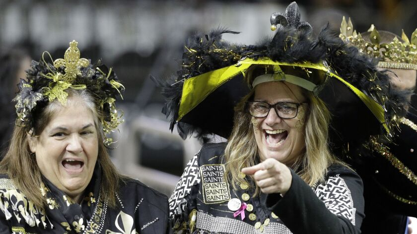 Saints fans gather at the Mercedes-Benz Superdome before Sunday's NFC championship game against the Rams.