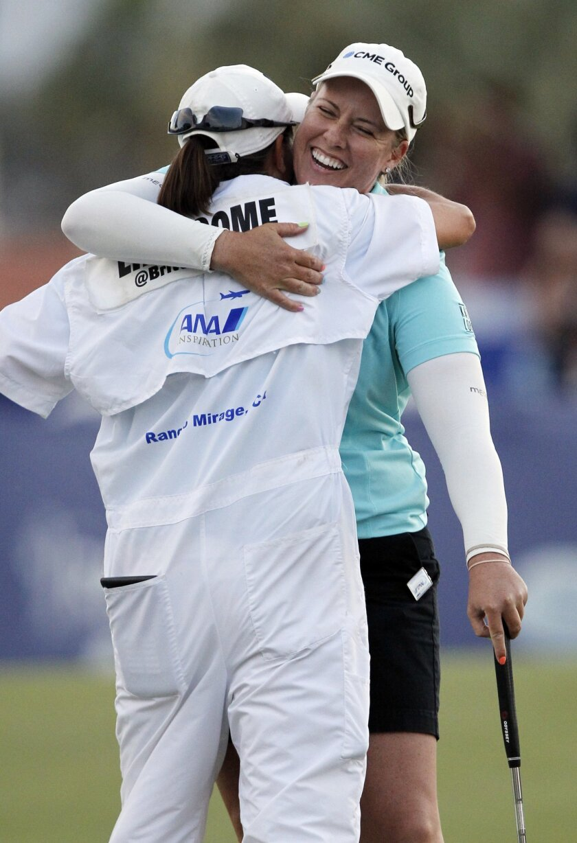 Brittany Lincicome, right, hugs her caddie, Missy Pederson, after winning on the third playoff hole during the final round of the LPGA Tour ANA Inspiration golf tournament at Mission Hills Country Club in Rancho Mirage, Calif., Sunday, April 5, 2015. (AP Photo/Alex Gallardo)