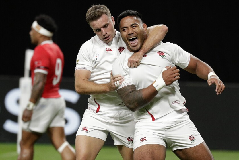 England's Manu Tuilagi, right, is congratulated by teammate George Ford after scoring his second try during the Rugby World Cup Pool C game at Sapporo Dome between England and Tonga in Sapporo, Japan, Sunday, Sept. 22, 2019. (AP Photo/Aaron Favila)