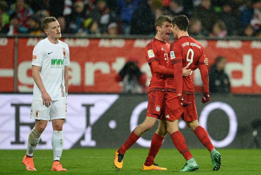 Thomas Mueller , second right, and Robert Lewandowski, right,  of Munich celebrate after the  opening goal  during the German Bundesliga soccer match between FC Augsburg and Bayern Munich at the WWK-Arena in Augsburg, Germany, Sunday Feb. 14, 2016.  On the left is Augsburg's  Philipp Max. (Andreas