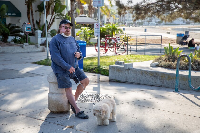 Ray Hamel and Popcorn, a Maltese poodle, take a break at Fanuel Street Park in Pacific Beach.