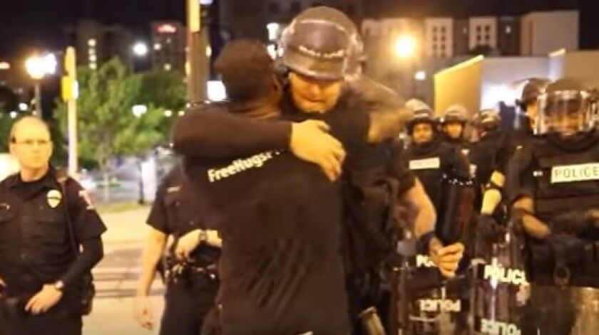 Ken Nwadike Jr. is seen in this screen grab from YouTube video hugging police officers during a night of unrest in North Carolina.