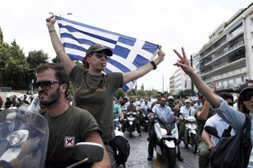 A striking Municipal police officer on motorcycle holds a Greek flag during a protest, in central Athens, on Thursday, July 11, 2013. Public sector unionists and municipality workers staged a protest Thursday against new austerity measures that will push thousands of public sector workers out of work or placed in a mandatory transfer program. (AP Photo/Petros Giannakouris)