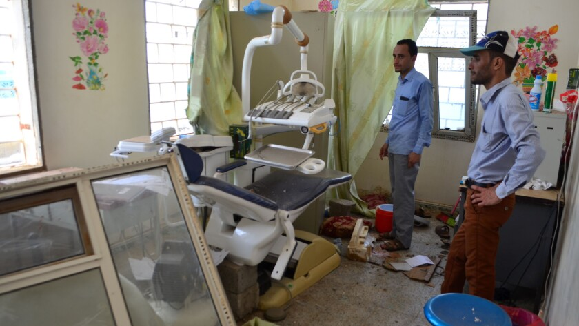 Men inspect the damages at a hospital in Abs, Hajjah, Yemen, on Aug. 16, 2016, a day after an airstrike by a Saudi-led coalition.
