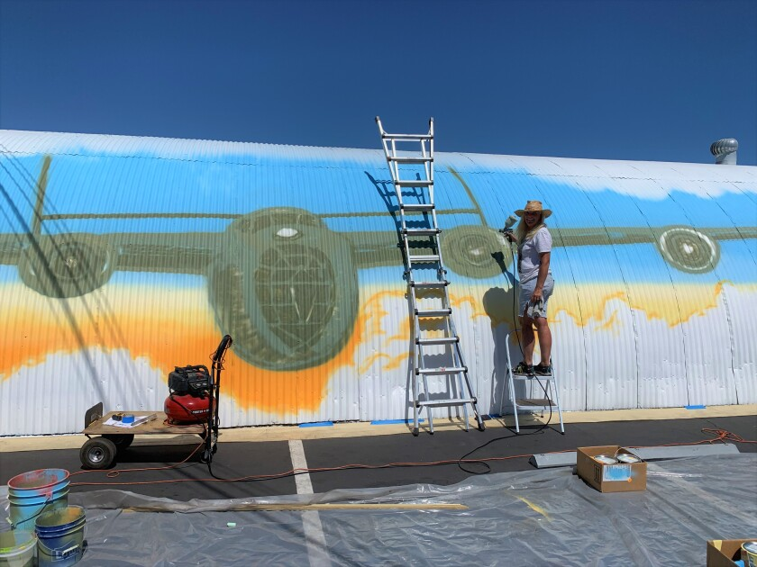 Nancy Hadley is working on a mural of a Consolidated B-24 Liberator bomber on the former Santa Ana Army Air Base site.