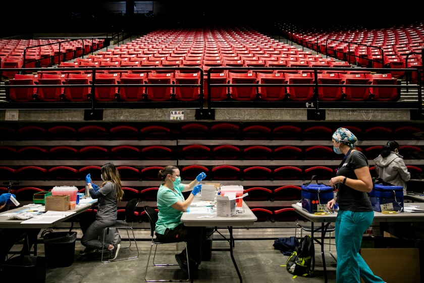 Resident Nurse Jasmine Bombart fills a dose of the Pfizer Covid-19 vaccine at Viejas Arena at San Diego State University.