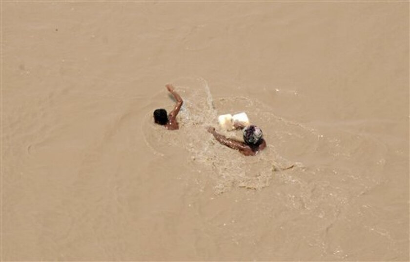 Pakistani villagers swim across floodwaters after collecting relief supplies dropped from an army helicopter in a heavy flood-hit area of Mithan Kot, in central Pakistan, Monday, Aug. 9, 2010. The government has struggled to cope with the scale of the disaster, which has killed at least 1,500 peopl