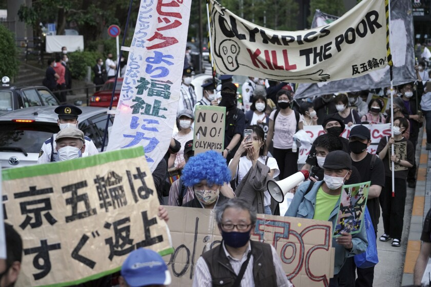 Protesters hold anti-Olympic signs in Japanese and English.
