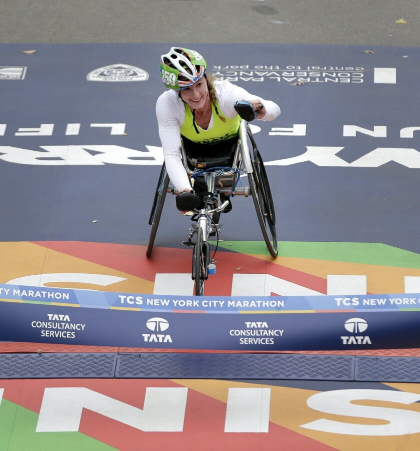 Tatyana McFadden, of the United States, crosses the finish line first in the women's wheelchair division at the 2015 New York City Marathon in New York, Sunday, Nov. 1, 2015.  (AP Photo/Seth Wenig)