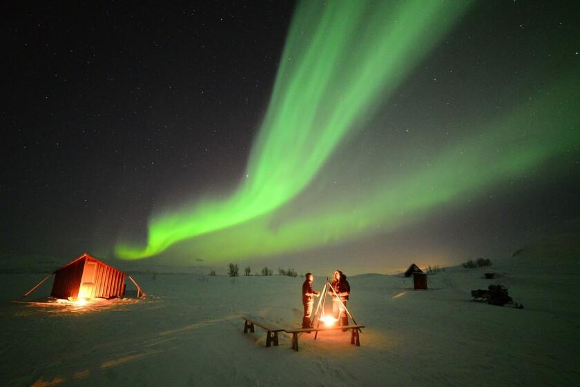 Travelers watch the northern lights dance over the Aurora Village in Björkliden, Sweden.