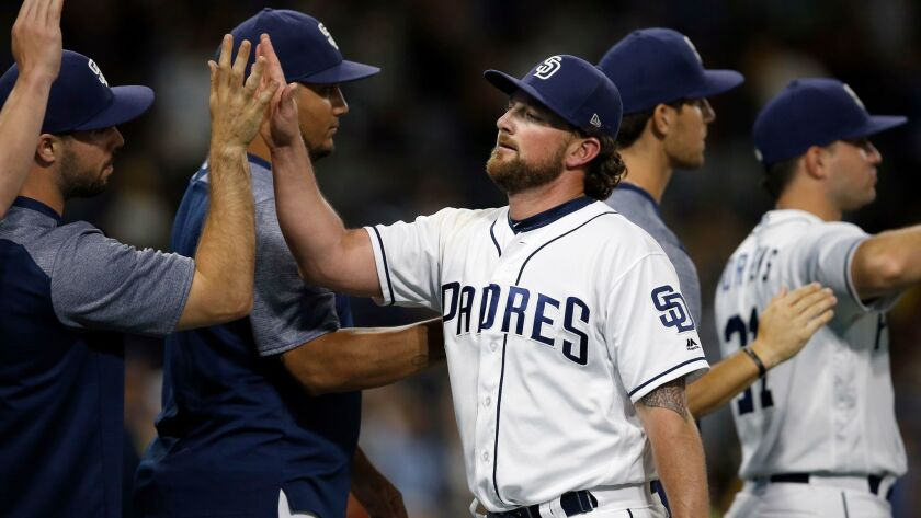 Padres relief pitcher Kirby Yates, center, gets congratulated by teammates after the Padres defeated the Pittsburgh Pirates 4-2 in a baseball game in San Diego, Saturday, July 29, 2017.