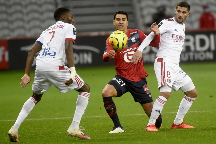 Lille's French midfielder Benjamin Andre, center, is challenged by Lyon's French midfielder Houssem Aouar, right, during the French League One soccer match between Lille and Olympique Lyonnais at the Pierre-Mauroy Stadium in Villeneuve d'Ascq, northern France, Sunday, Nov. 1, 2020. (Francois Lo Presti, Pool via AP)
