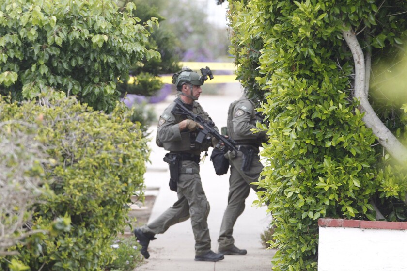 """San Diego police SWAT surrounded a house on Del Mar Avenue west of Cable Street in Ocean Beach Wednesday as they searched for a man considered a """"person of interest"""" in the death of a woman found inside a garage on Niagara Avenue."""