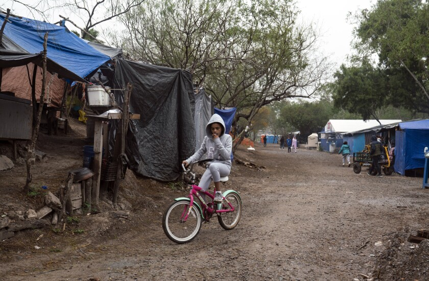 A girl rides her bike in a migrant camp in Matamoros, Mexico.