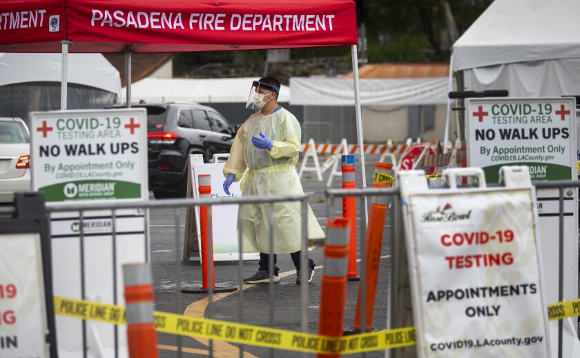Healthcare worker speak with drivers at a coronavirus testing site in Pasadena in May.