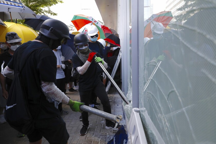 FILE - In this July 1, 2019, file photo, protesters try to break the glass walls of the Legislative Council in Hong Kong. From across the political spectrum, Hong Kong residents condemned mob violence at the U.S. Capitol, 18 months after they saw protesters storm their own local legislature. (AP Photo/Vincent Yu, File)