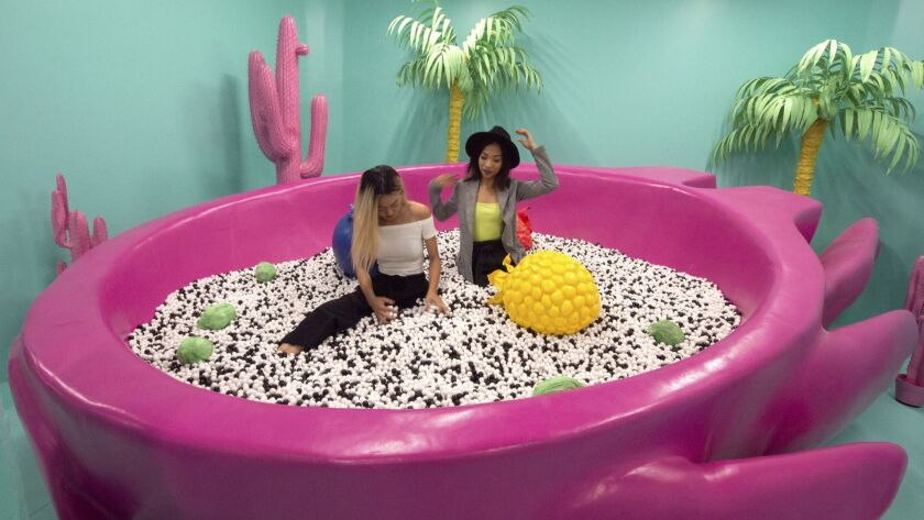Stacy Ju (left) and Kwihn Pham (right) enjoy the Dragon Fruit Pool, filled with plastic beads, in th